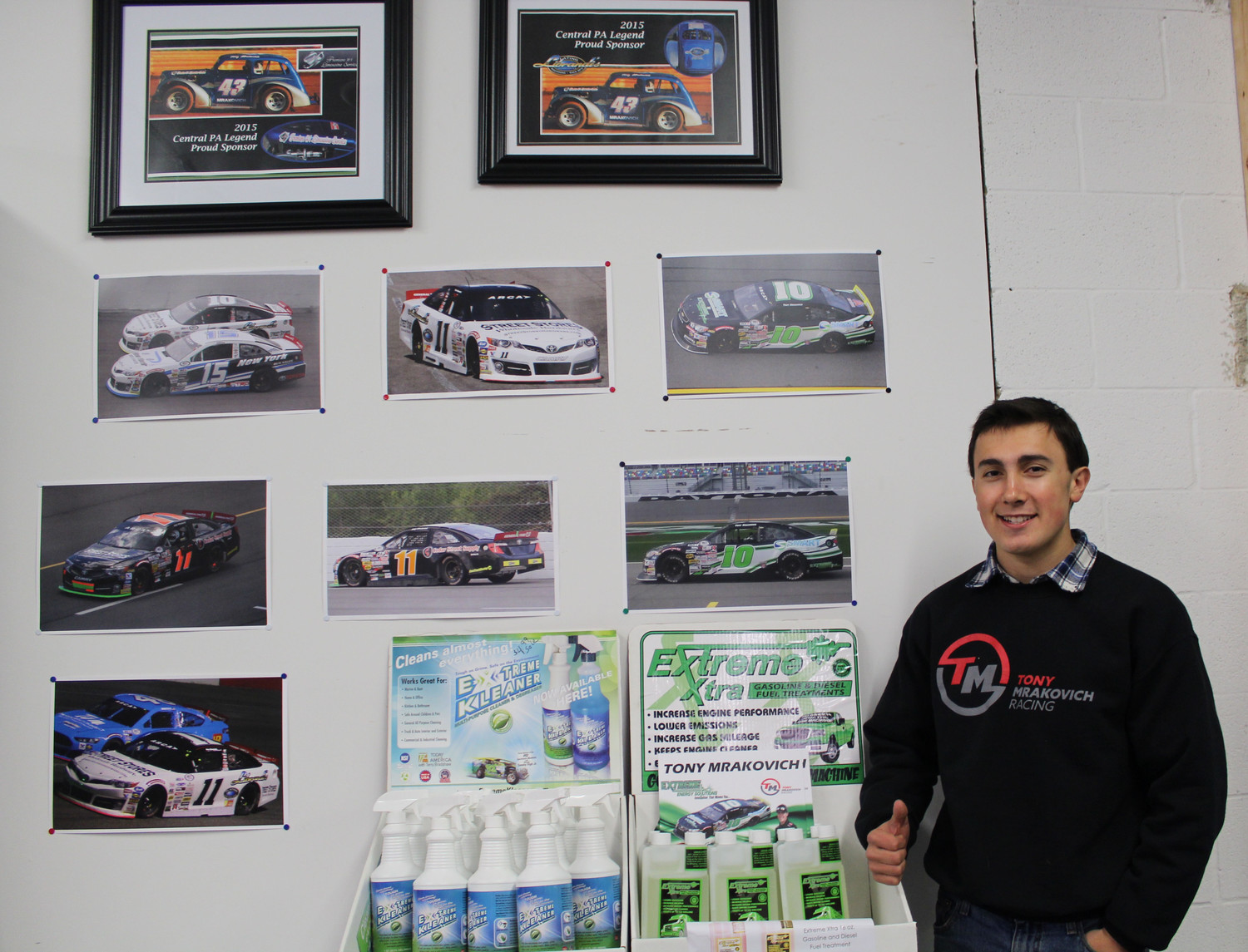 Tony Mrakovich stands in front of a pictures of his racing cars.