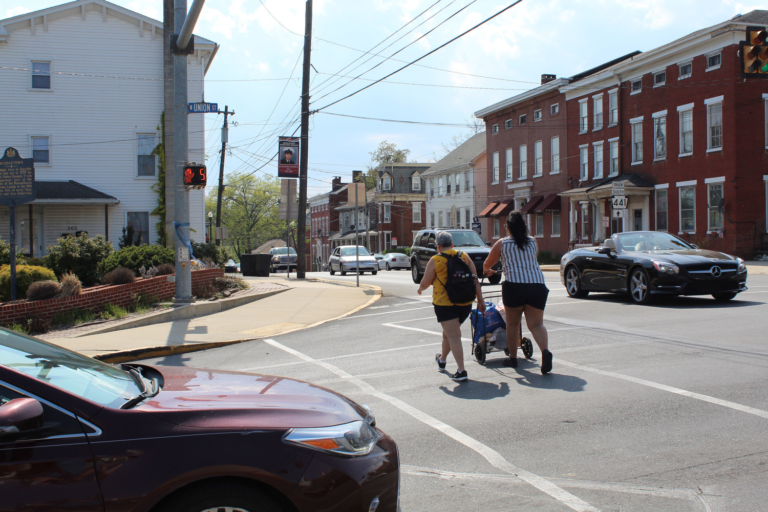 Destinee Flores and Millie Mateo cross Main Street on Thursday, May 3.