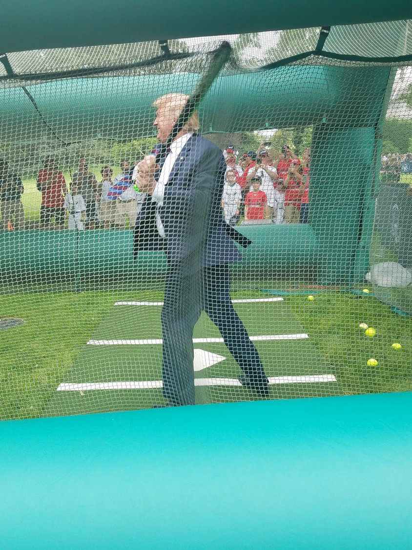 President Donald Trump takes a swing in the batting cage during the field day May 30.