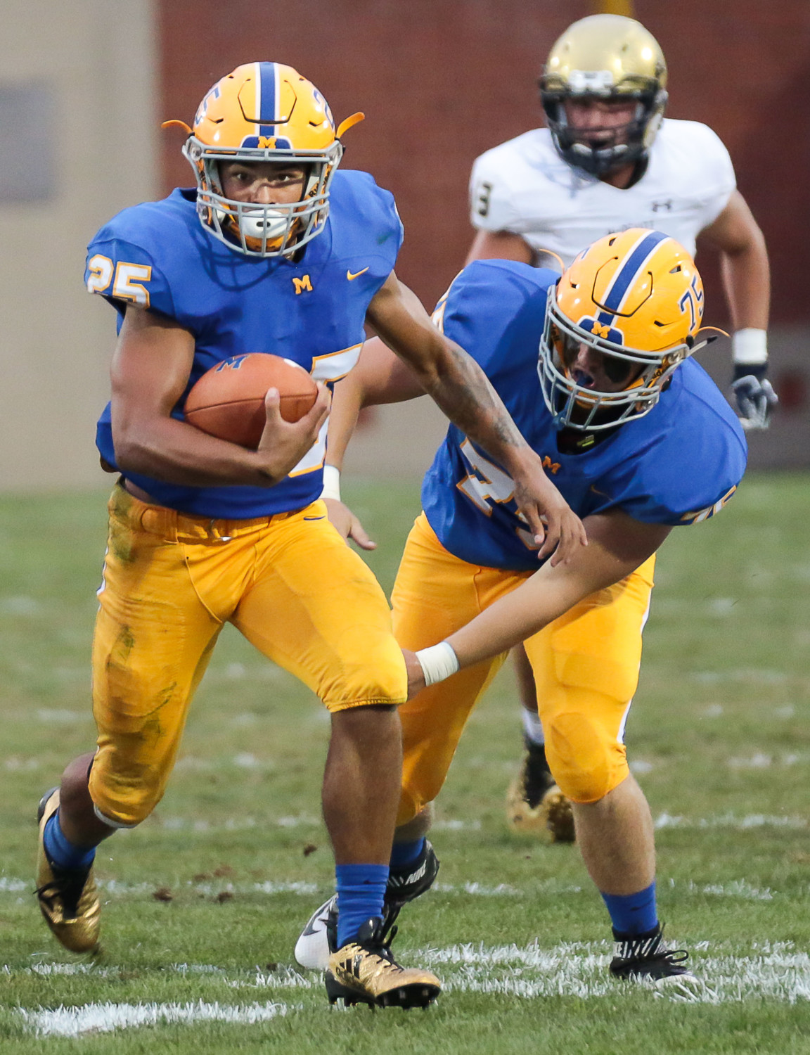 Jose Lopez runs in front of Morgan Billman in Friday's 40-14 loss to Bishop McDevitt at War Memorial Field.