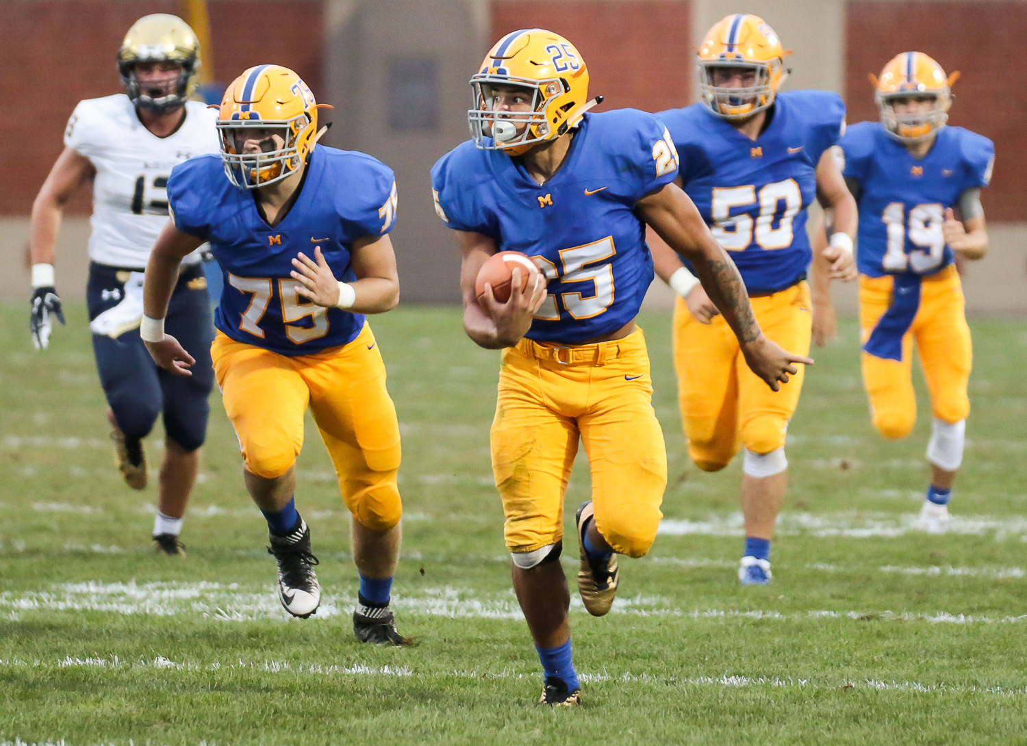 Jose Lopez runs in front of Morgan Billman, Joe Gusler and Scott Ash in Friday's 40-14 loss to Bishop McDevitt at War Memorial Field.
