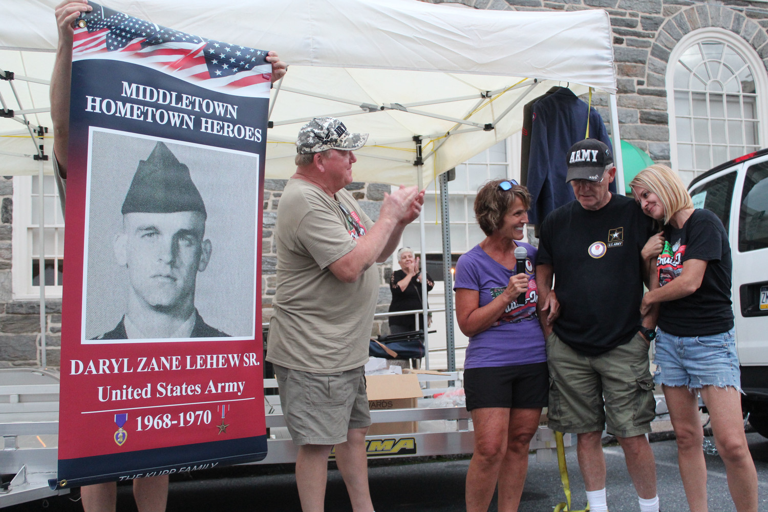 Nicole Besic, right, hugs her father, Daryl Lehew, on Thursday as Irvin Turpin Jr. claps and Carol Kupp watches. The Kupps had a Middletown Hometown Heroes banner made for Lehew, a U.S. Army veteran, which is now on top of Kuppy's Diner. Turpin, an Air Force veteran, also received a banner.