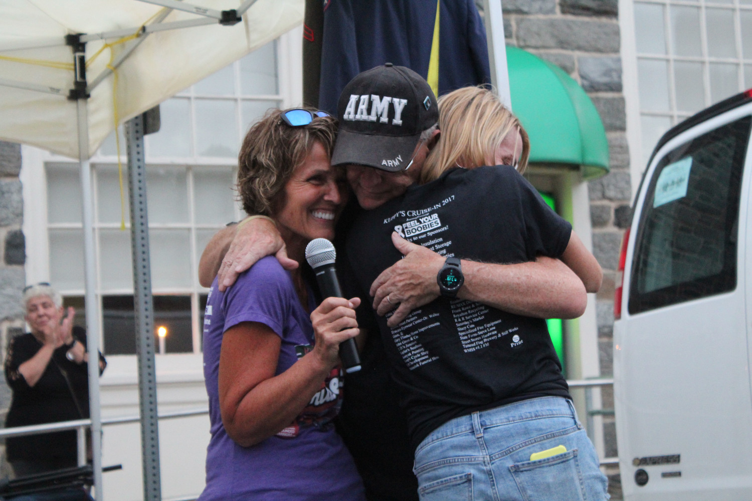 Daryl Lehew hugs Carol Kupp and his daughter Nicole Besic after his Middletown Hometown Heroes banner was unveiled.