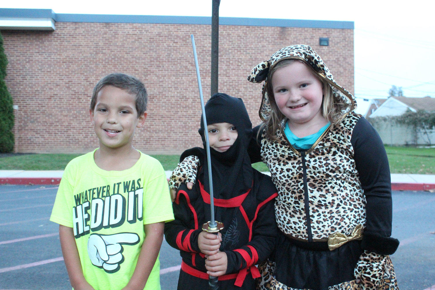 Aiden Donar, Jason Powell Jr. and Ava Powell wait for the Halloween parade on Oct. 16.