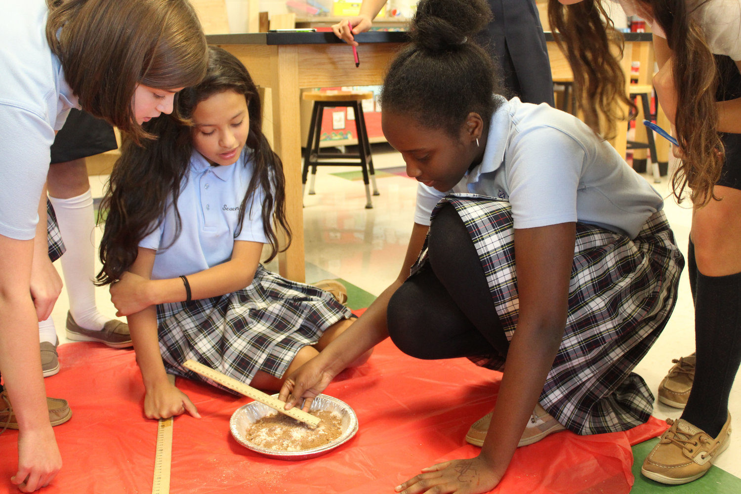"Emma Still, Paulina Torres and Janelle King measure ""craters"" caused by marbles made to mimic the craters on the moon during class on Oct. 24."