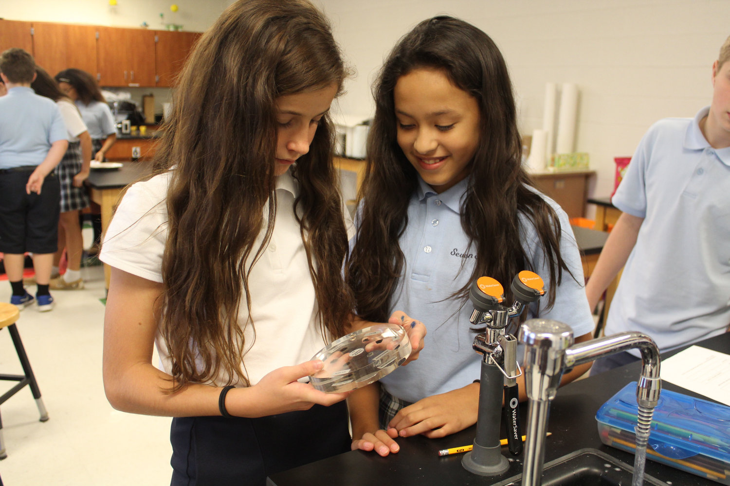 Cathleen Mooney and Paulina Torres look at lunar rock samples during class on Oct. 24.