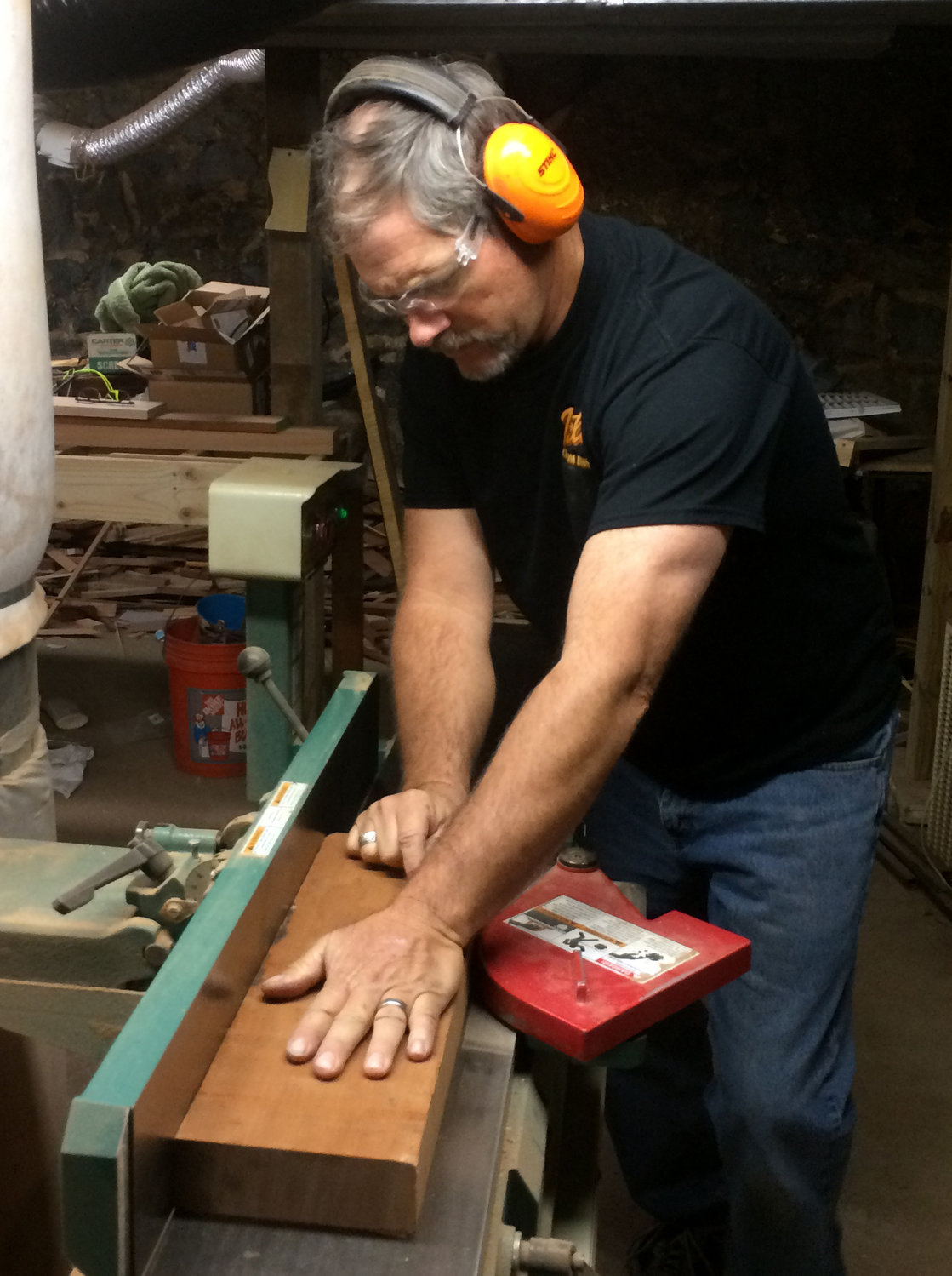 Darryl Betts works on a piece of wood that has been cut down to fit one of the body wings of a bass guitar. Here he is joining the piece to get it perfectly flat and square, before planing to thickness and marking with a template to cut the piece out.