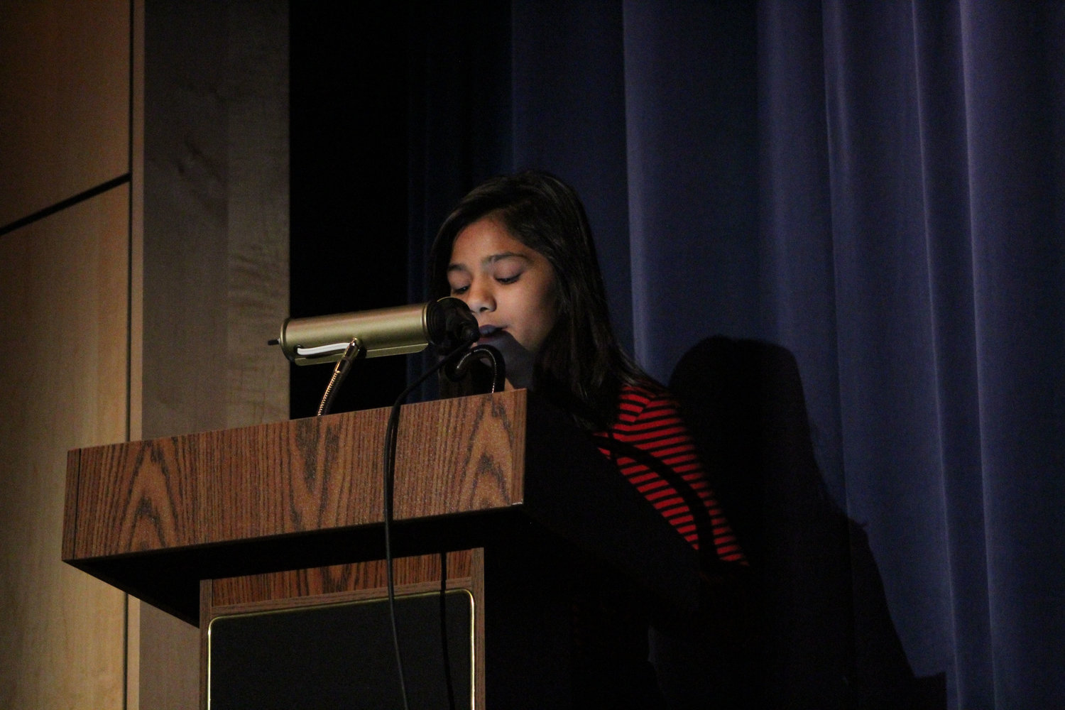 Sixth-grader Aman Azim reads her essay during the Veterans Day Program Nov. 9.