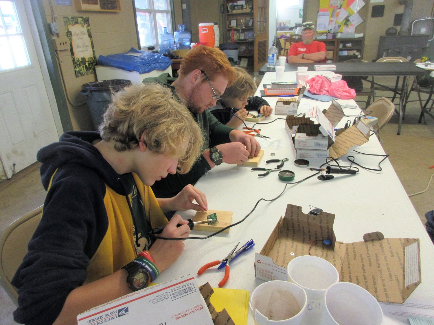 Brock Leach, Kyle Hoyt and Jesse Reigle try their hand at soldering circuit boards during the electronics merit badge.