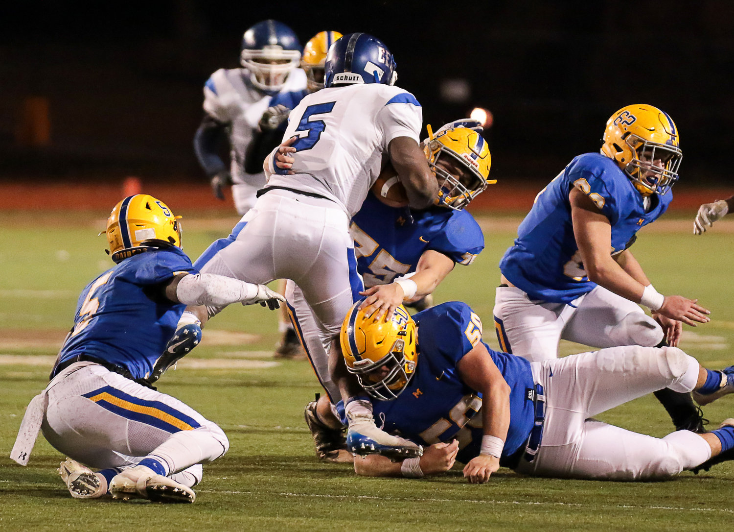 Middletown's Travyon Joseph (No. 5), Morgan Billman (No. 75), Joe Gusler (No. 50) and Cole Senior (No. 62) work on bringing down the ball carrier during Middletown's 21-14 win over Conwell-Egan at Milton Hershey High School in the PIAA 3A state quarterfinals Nov. 23.