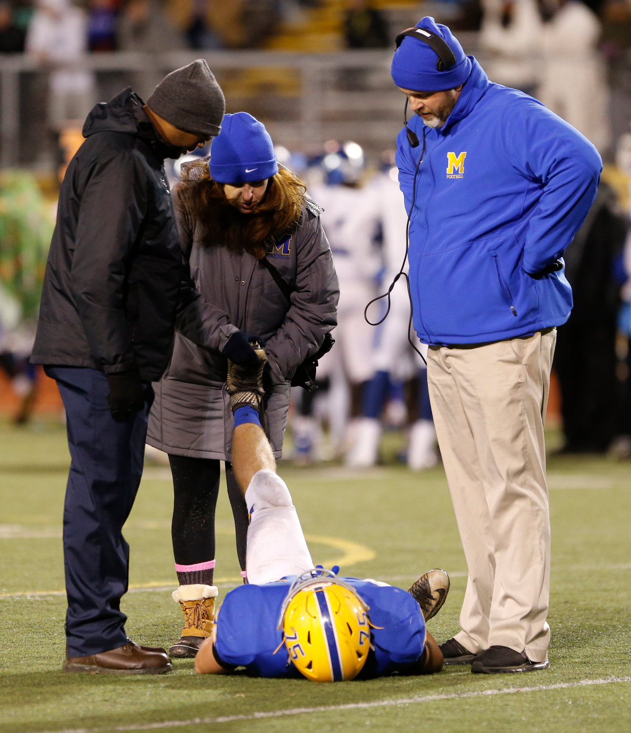 Head coach Brett Myers watches trainers work on Morgan Billman during Middletown's 21-14 win over Conwell-Egan at Milton Hershey High School in the PIAA 3A state quarterfinals Nov. 23.