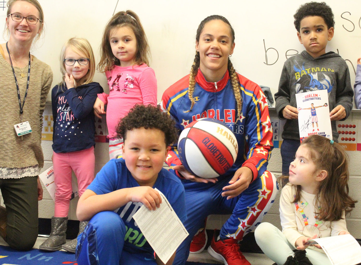 "Harlem Globetrotter Briana ""Hoops"" Green surprised Kyrie Peay, front left, in his preschool classroom at Seven Sorrows on Feb. 13 with a jersey and tickets."