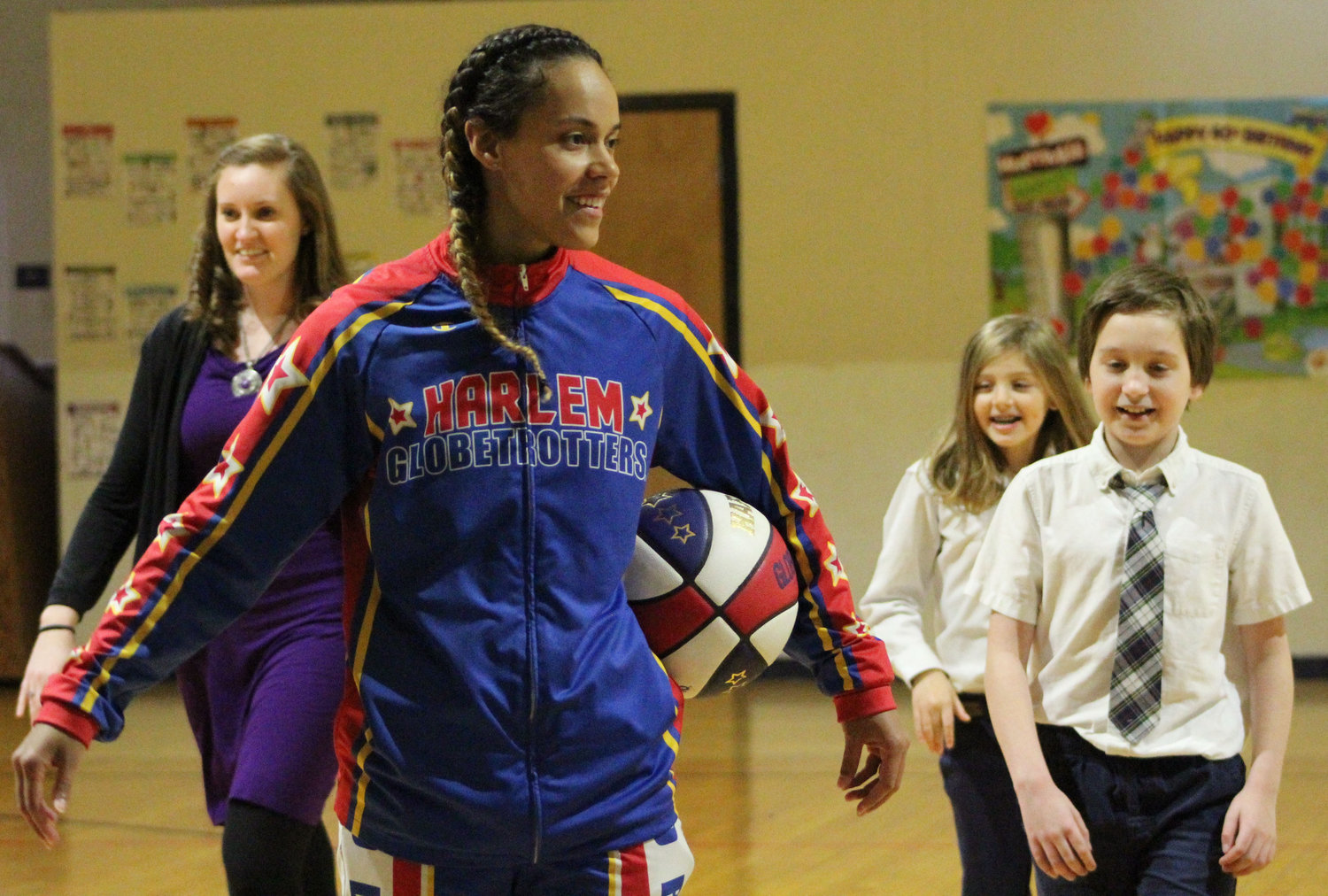 "Harlem Globetrotter Briana ""Hoops"" Green talks about teamwork and bullying with Seven Sorrows of the Blessed Virgin Mary students on Feb. 13. Green surprised preschooler Kyrie Peay with a jersey and tickets."