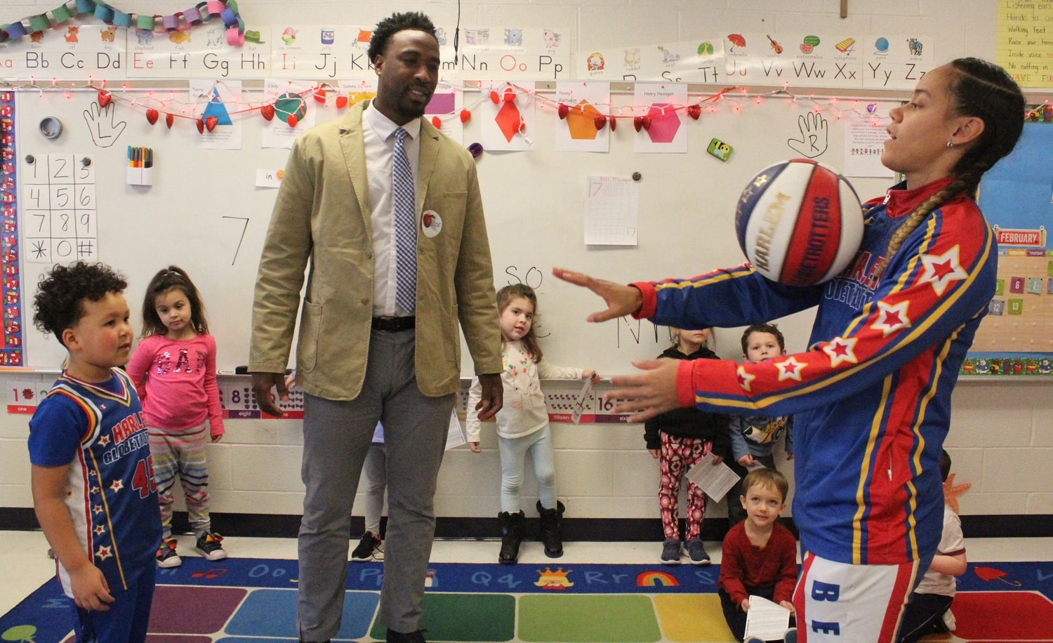 "Harlem Globetrotter Briana ""Hoops"" Green shows Kyrie Peay and his father, Josiah, basketball tricks Feb. 13."