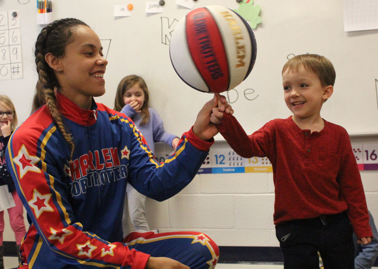 "Harlem Globetrotter Briana ""Hoops"" Green shows Landon Matson how to spin a ball on his finger at Seven Sorrows on Feb. 6."