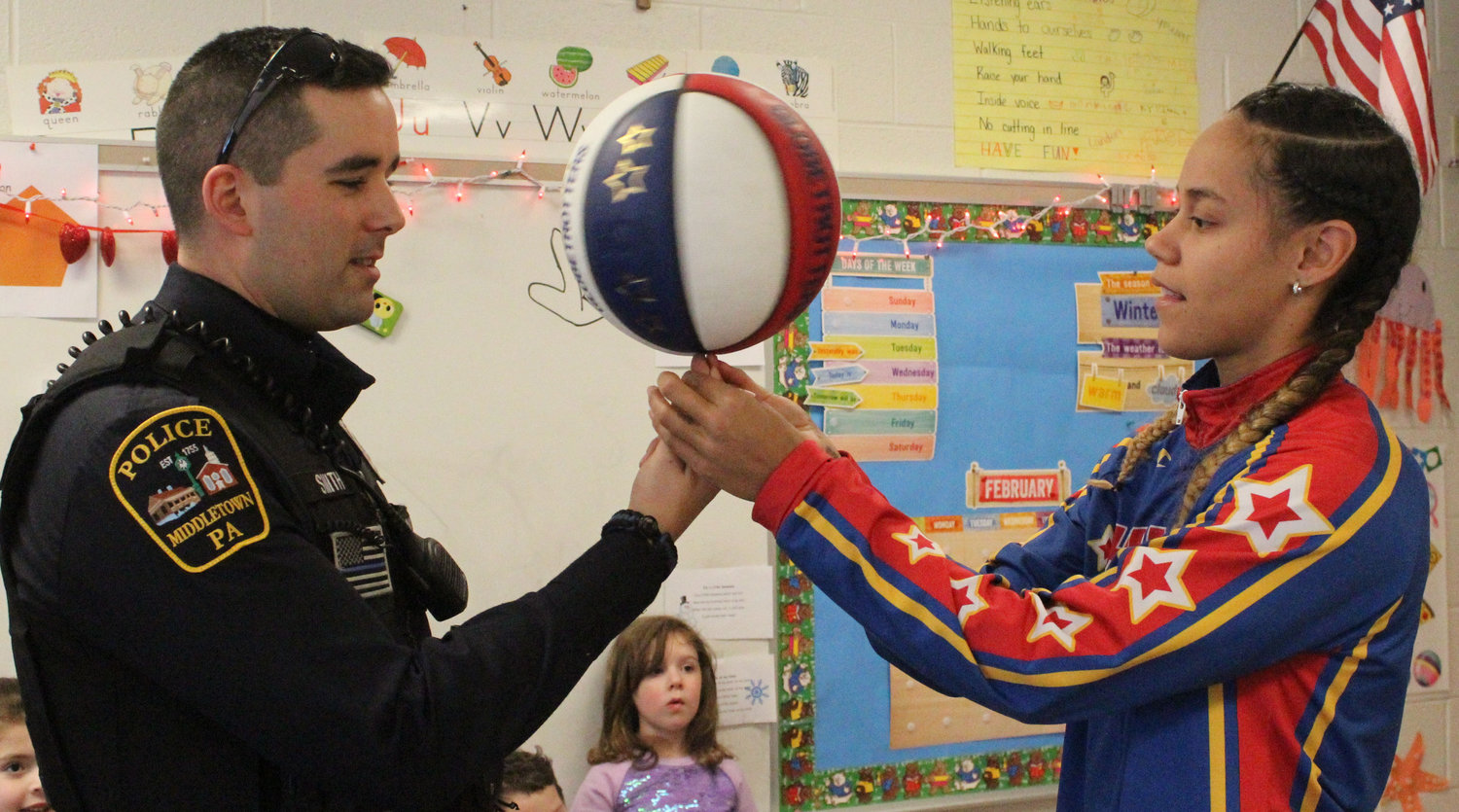 "Harlem Globetrotter Briana ""Hoops"" Green shows Middletown Patrolman Joseph Smith how to spin a basketball on his finger Feb. 6. She surprised Kyrie Peay in his preschool classroom at Seven Sorrows  with a jersey and tickets."