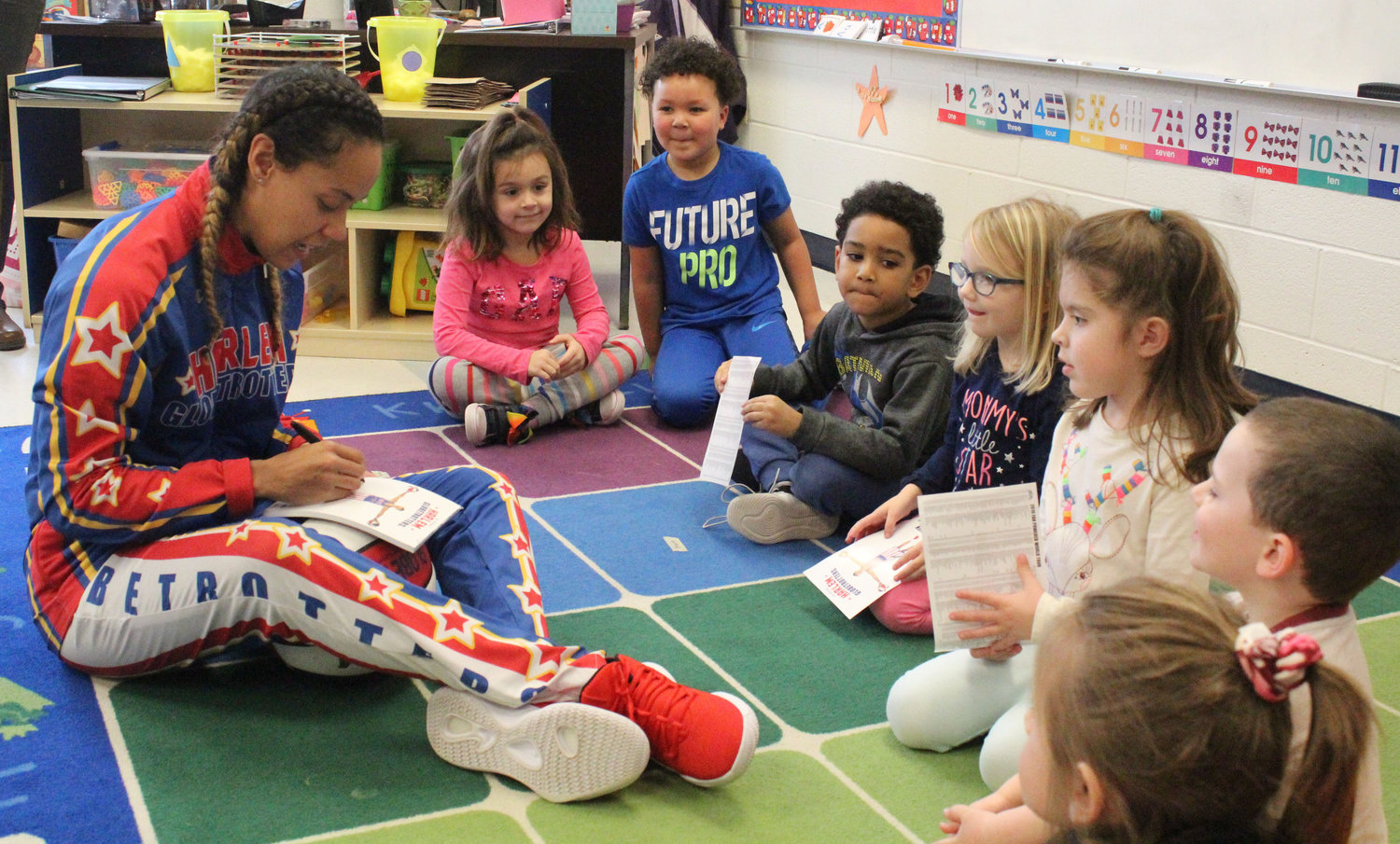 "Harlem Globetrotter Briana ""Hoops"" Green signed autographs for Seven Sorrows preschool students Feb. 6 She surprised preschooler Kyrie Peay with a jersey and tickets."