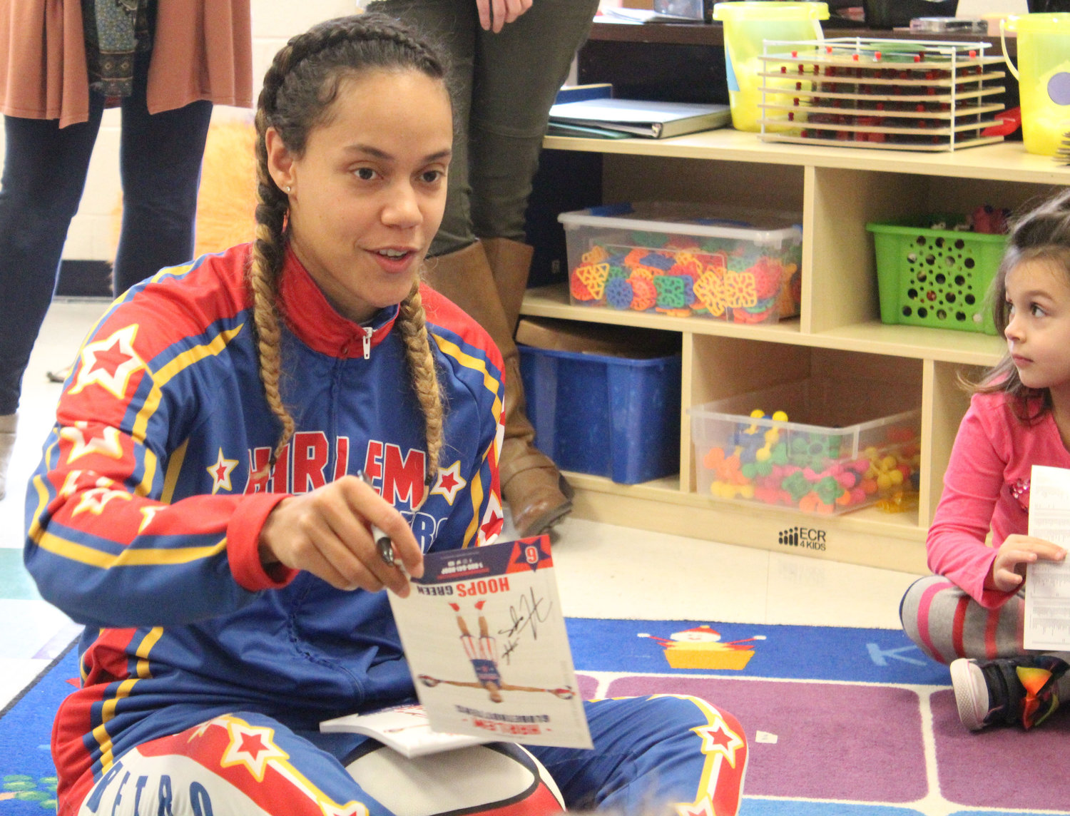 "Harlem Globetrotter Briana ""Hoops"" Green signed autographs for Seven Sorrows preschool students Feb. 6. She surprised preschooler Kyrie Peay with a jersey and tickets."