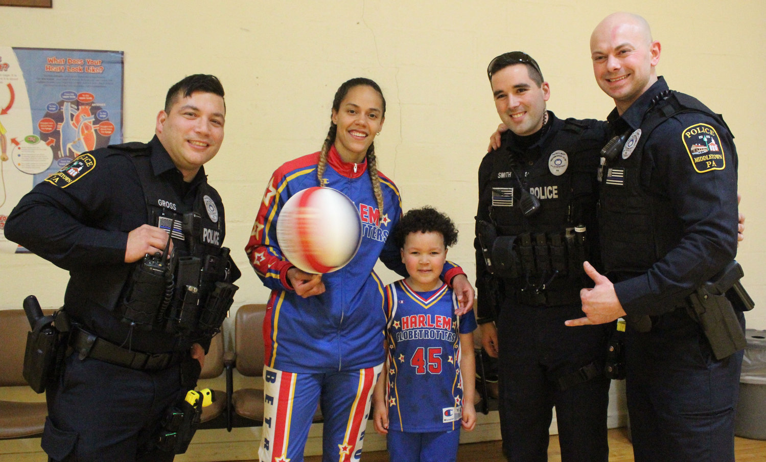 "Harlem Globetrotter Briana ""Hoops"" Green took a picture with Kyrie Peay and Middletown Police Officers Cameron Gross, Joseph Smith and Adam Tankersley on Feb. 13. Green surprised Kyrie with a Globetrotter jersey and tickets at Seven Sorrows."