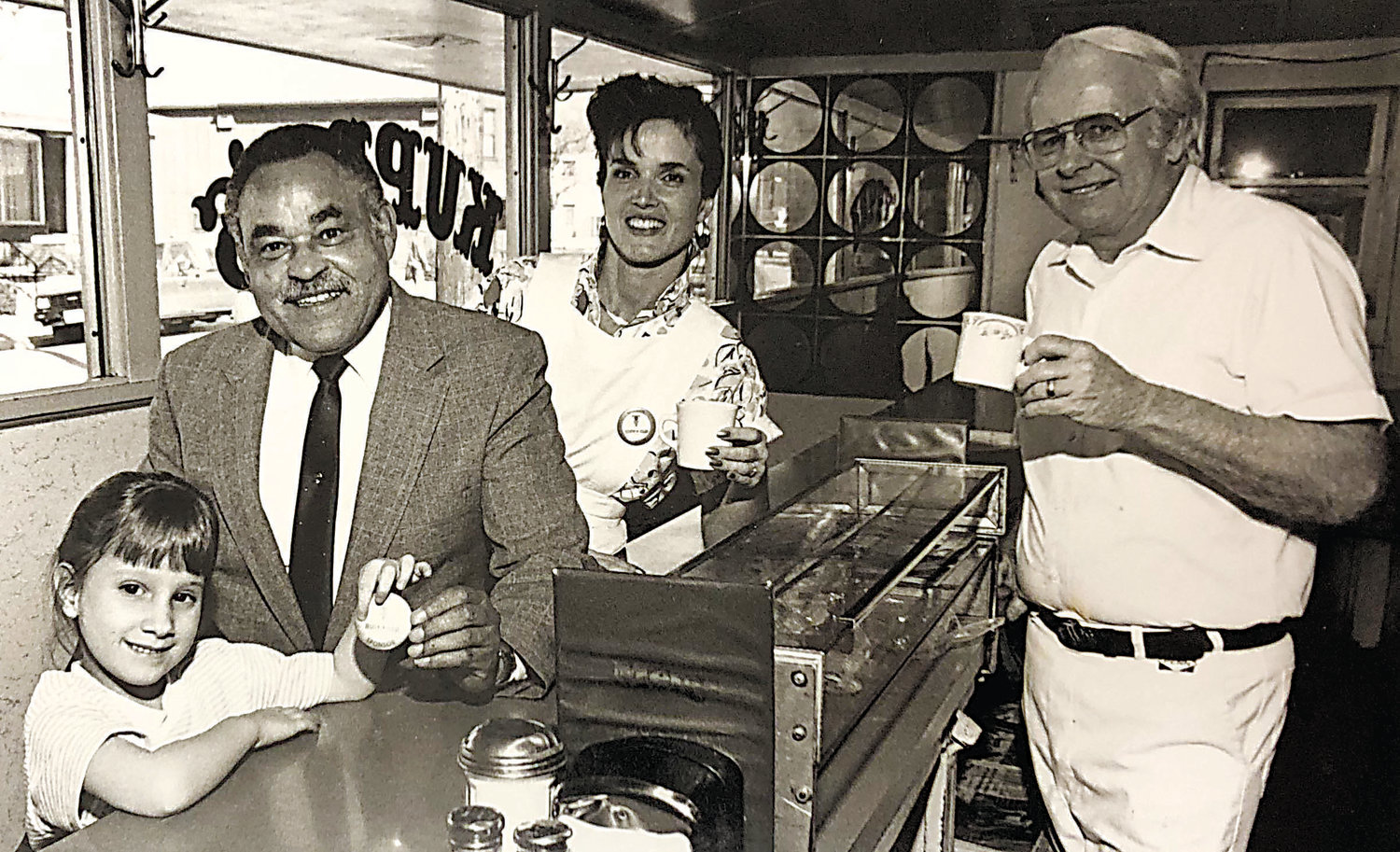 In this photo from the 1980s, Mayor Robert Reid poses with Carol Kupp and Karl Kupp at Kuppy's Diner. The girl on the left is unidentified.