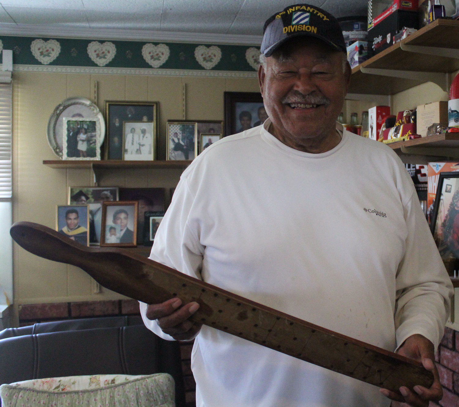 Robert Reid holds a paddle made for him by his students. It is on display in a room in his home.