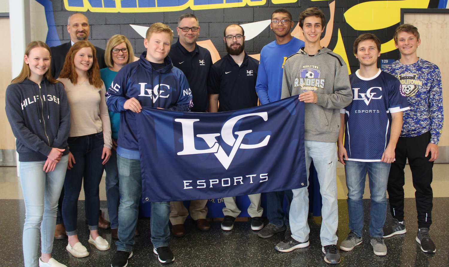 Mason Garza, center left, poses with friends, family, MAHS staff and Lebanon Valley College staff after being presented with a scholarship to participate on LVC's Esports team on March 14.