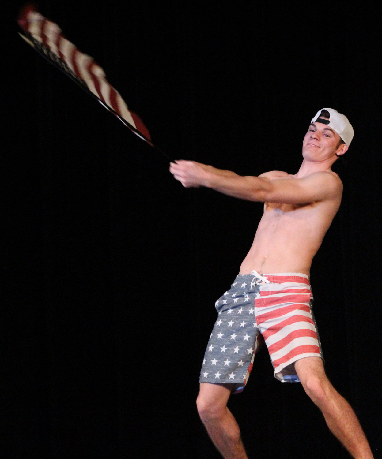 Scott Ash waves an American flag during Mr. Middletown on March 29.