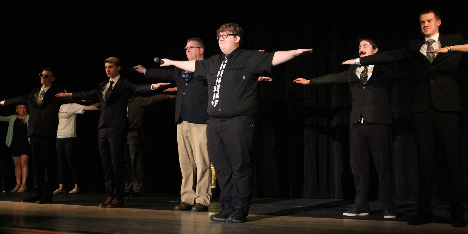 Nick Holmes leads the contestants and the crowd in a T-pose during Mr. Middletown on March 29.