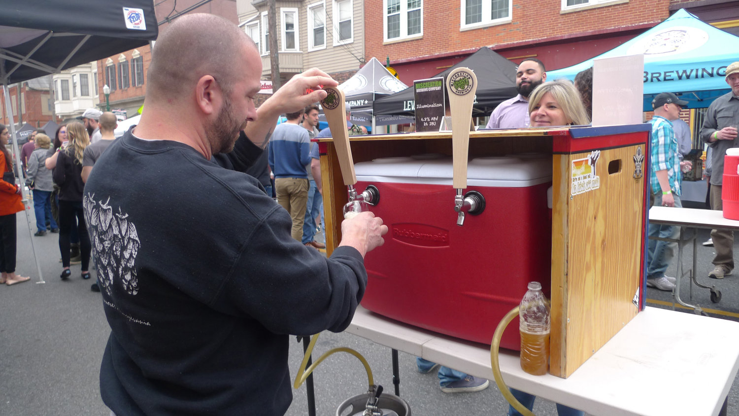 Brent Stambaugh, owner of Miscreation Brewing Company from Hanover, pours a cup of his Anatomically Speaking IPA to Jenny Gerber of Elizabethtown who is waiting to sample it during the Little Little Beer Festival held on South Union Street in Middletown on May 1.