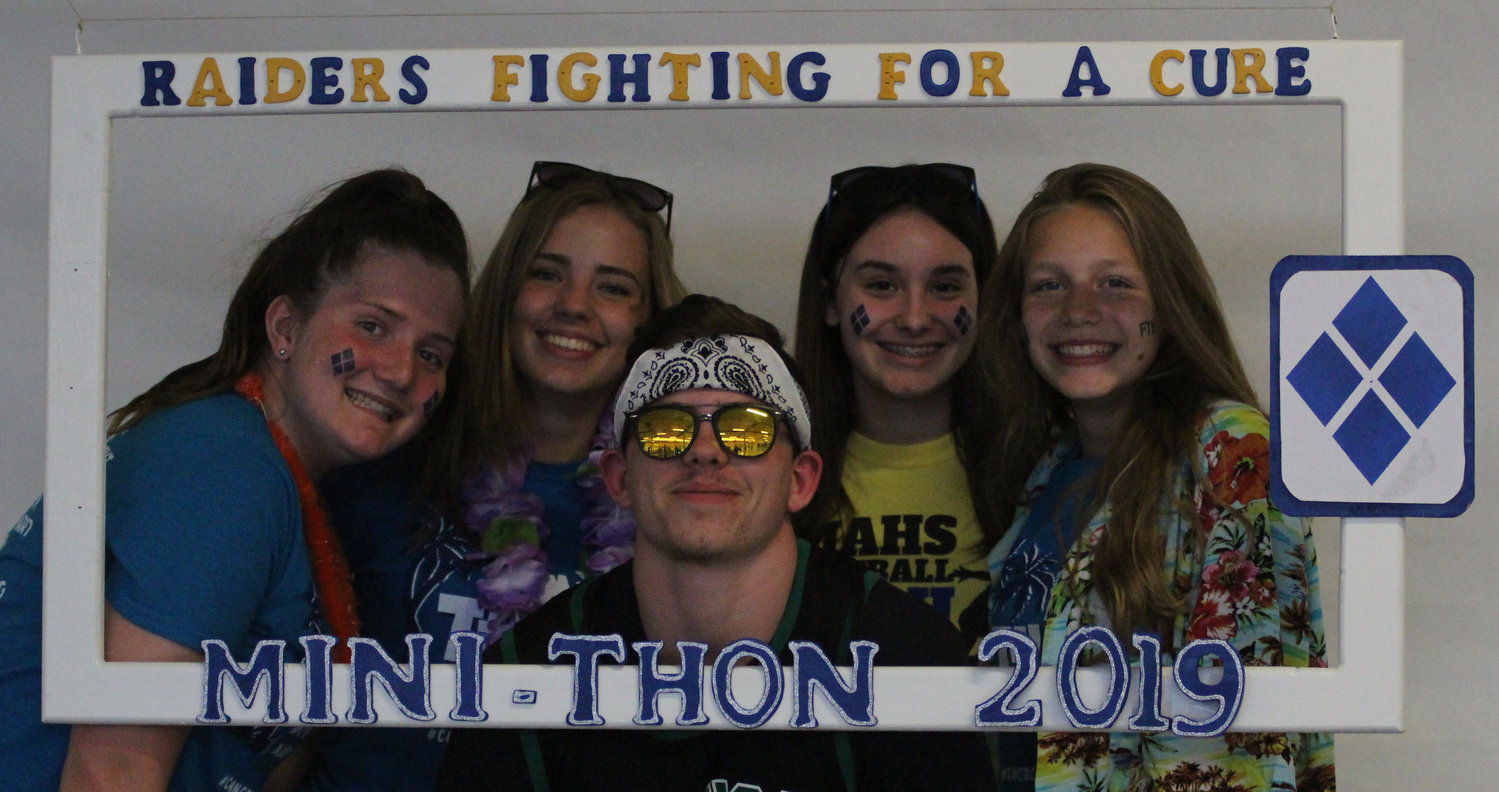 Emma Mitchell, Marissa Romberger, Jayson Stoner, Megan Gipe and Madison Zettlemoyer take advantage of the license plate holder photo frame at Middletown Area High School's Mini-THON on May 3.