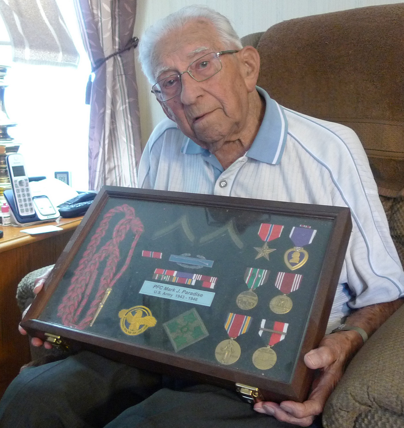 Mark Paradise sits in the living room of his home in Lower Swatara Township, holding the medals and the case he received after being honored at a ceremony in Carlisle Barracks in 2012.