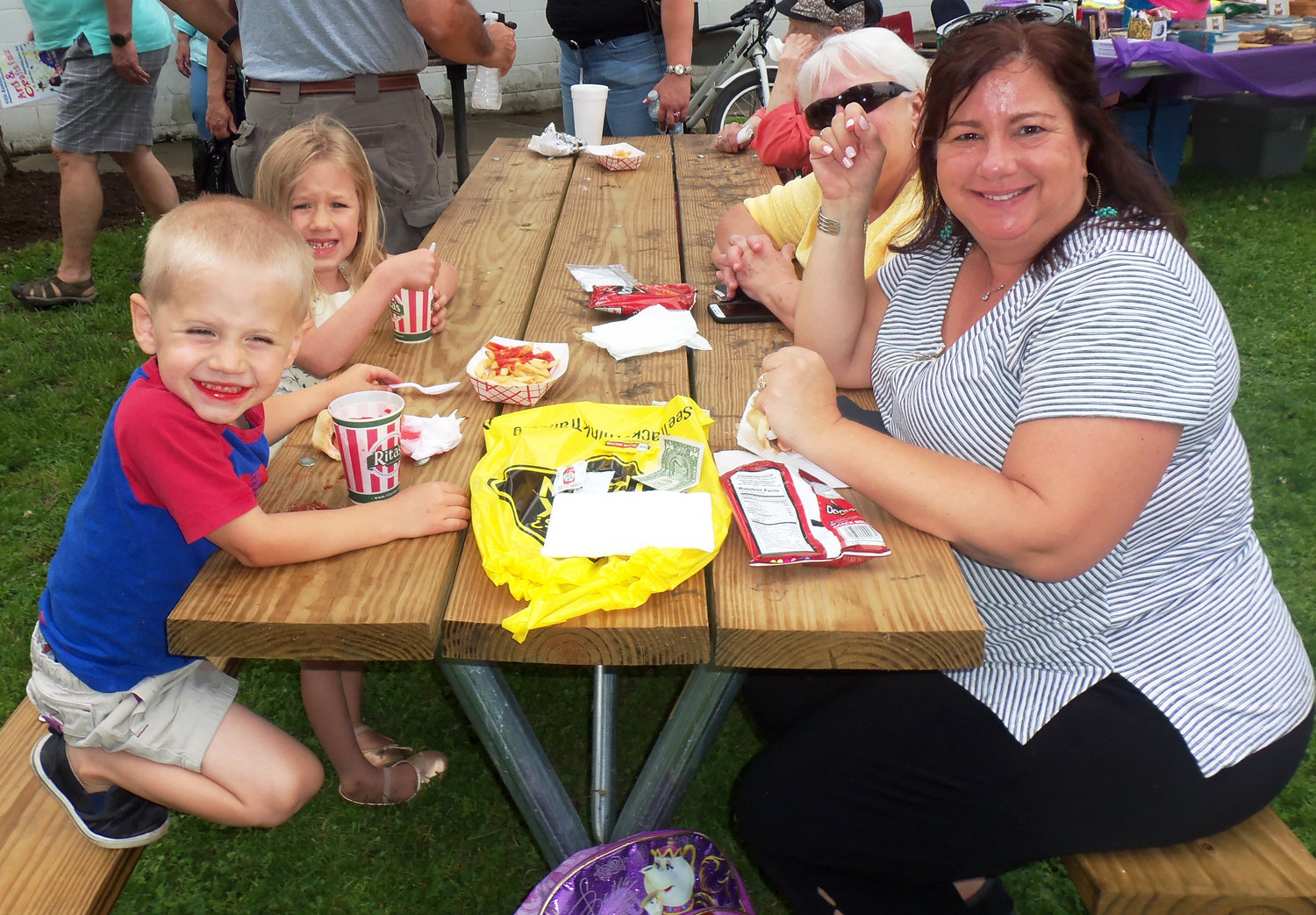 Erin Heverling of Hershey, front right, and children Mason, 3, and Olivia, 5, enjoy a picnic lunch at the Middletown Area Historical Society's Arts & Crafts Fair on June 8 with the children's grandmother, Ruth Dean of Hershey.