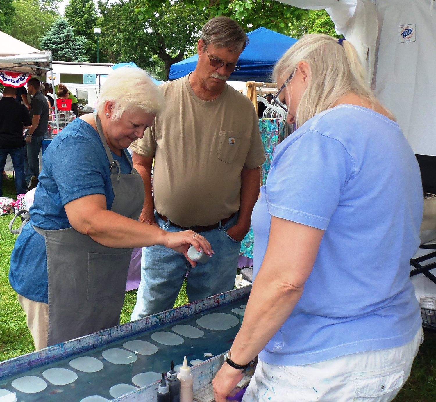 Sharon Moran of Middletown tries her hand at tie-dyeing a silk scarf as Stephanie Keleman, proprieter of Scarves Happen, offer instructions. Scarves Happen, of Swatara Township, was one of rougly 100 vendors participating in the Middletown Area Historical Society's Arts & Crafts Fair on June 8 at Hoffer Park.