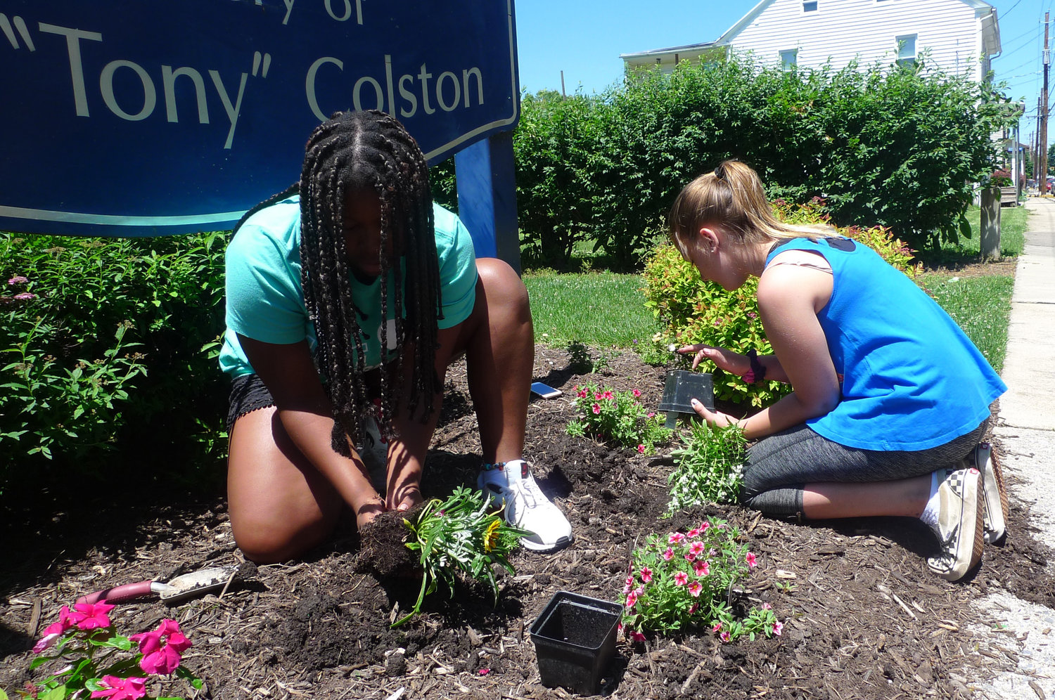 Ivory Parker of Genesis Court and Kiley Shomper of North Catherine Street plant new flowers at Colston Park on South Wood Street to replace ones that were ripped out by vandals on June 6. Both are members of the Middletown Communities That Care Youth Corps, which had just recently planted flowers and spread mulch in the park before their work was ruined by the vandals.