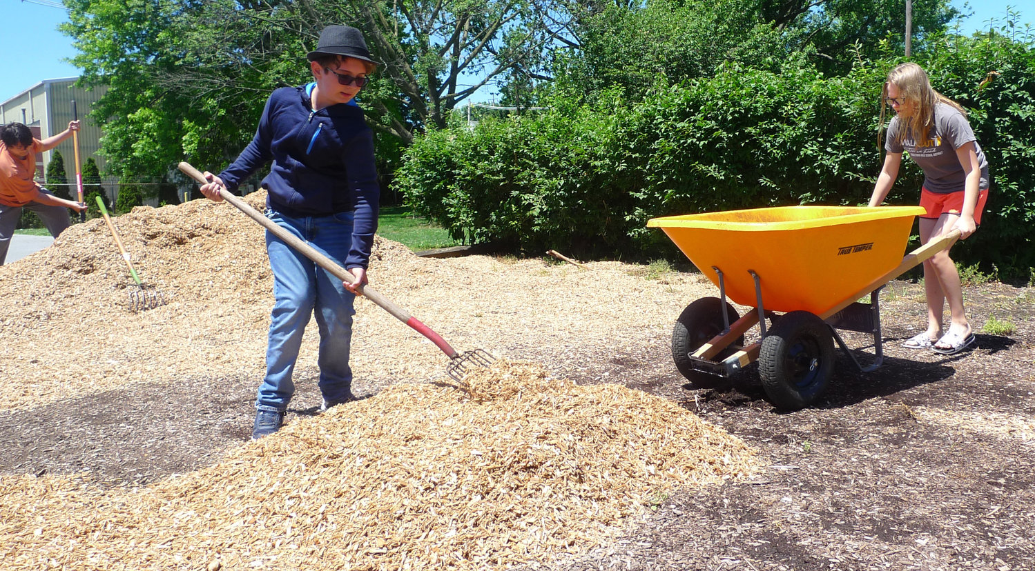 Middletown Communities That Care Youth Corps members Strummer Woodworth, of Hoffer Street, and Crystal Biesecker of Lower Royalton, spread new tan bark at Colston Park on South Wood Street, less than a week after the park had been hit by vandals on June 6.