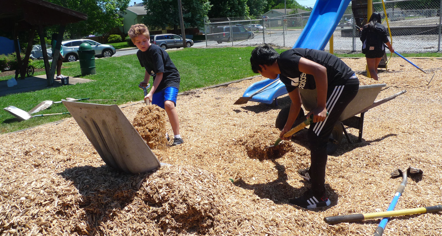 Jon Kuhn of North Spring Street and Robert Lian of North Pine Street in Middletown spread fresh tan bark in Colston Park on June 11, less than a week after the park was hit by vandals on June 6. Kuhn and Lian are both members of the Middletown Communities That Care Youth Corps, which had only recently planted flowers and spread mulch in the park before the vandals struck.