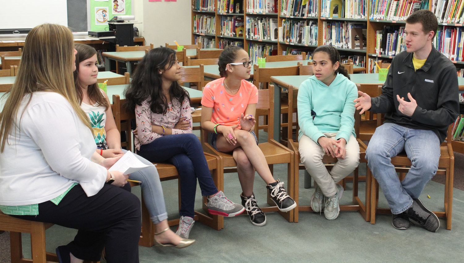 Raider Newscast reporter Tim Nevil, right, and instructional aide Christy Walker interview Ilianyeliz Lugo Soto, Ekmarie Curet Torres, Janielys Moreno Zambrana and Fatima Torres Rodriguez in April. The four recently moved to Middletown from Puerto Rico.