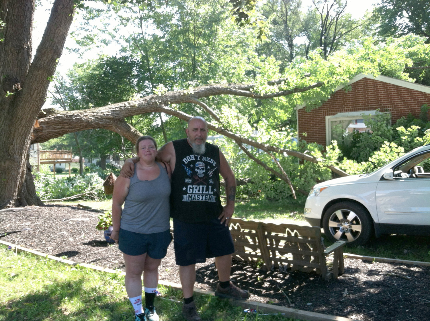 Michael and Angie Kachel stand in their front yard next to the tree that fell onto their house in the 1100 block of Vine Street in Middletown Thursday night.