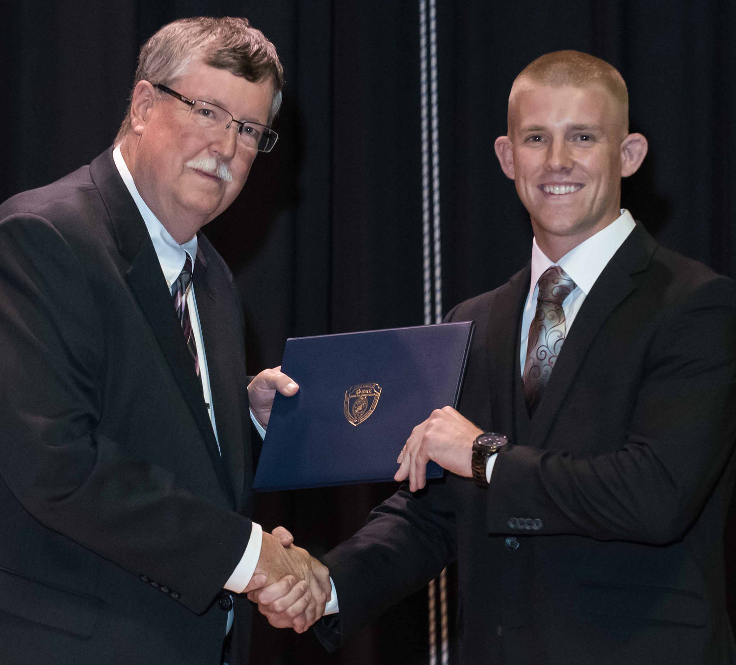 Todd Michael Houser Jr., right, is congratulated by Sgt. William Sindorf, a HACC Police Academy instructor and a retired Manheim Township police officer, for graduating in June.