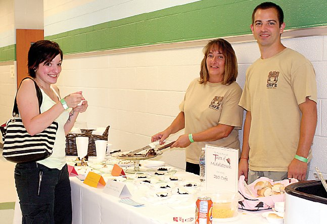 Debbie Reitz dishes out decadent desserts from The 230 Café at the Taste of Middletown, sponsored by Seven Sorrows BVM School. Marissa Toto, left, of Chambers Hill, said she enjoyed sandwiches and cake from the café. Reitz was helping her son, Nate Reitz,  right, who owns the 230 Café with brother Shelby.