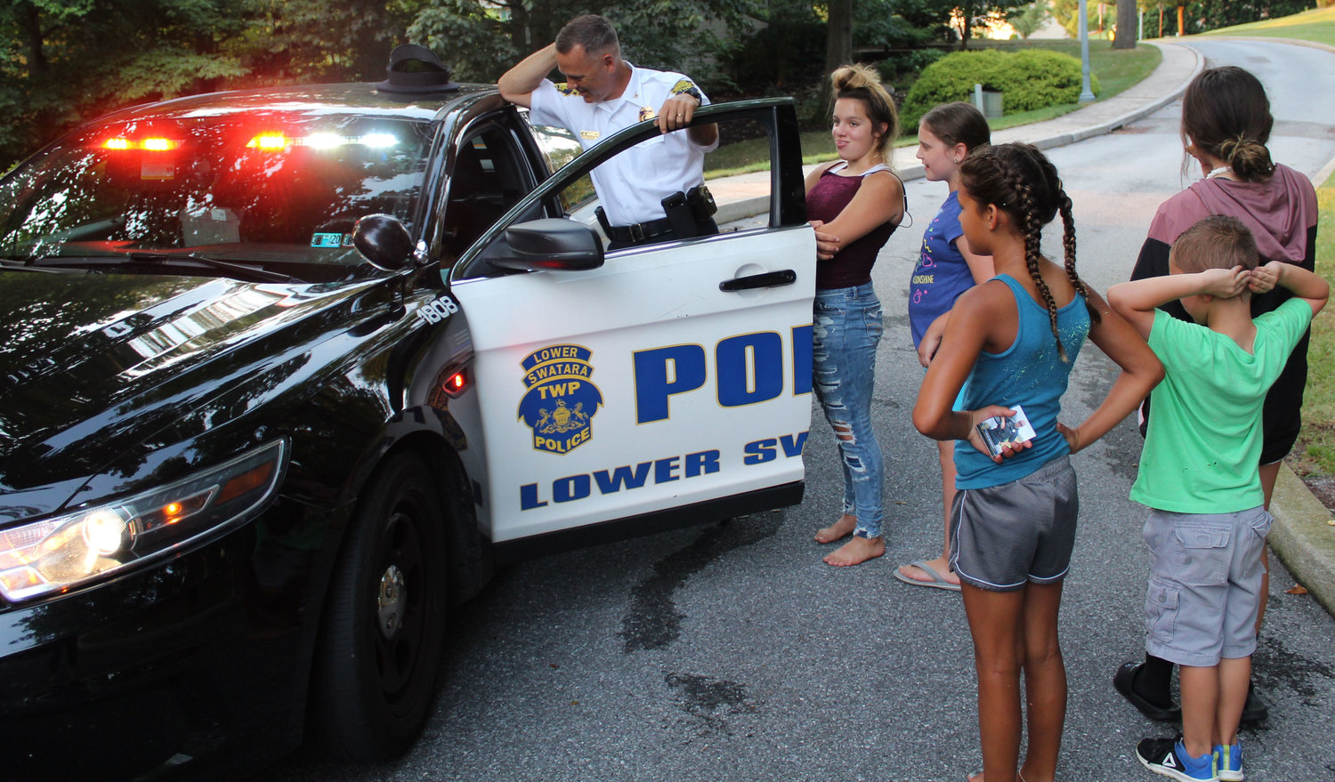 Kids line up to sit in Police Chief Jeff Vargo's patrol car during National Night Out Aug. 6.