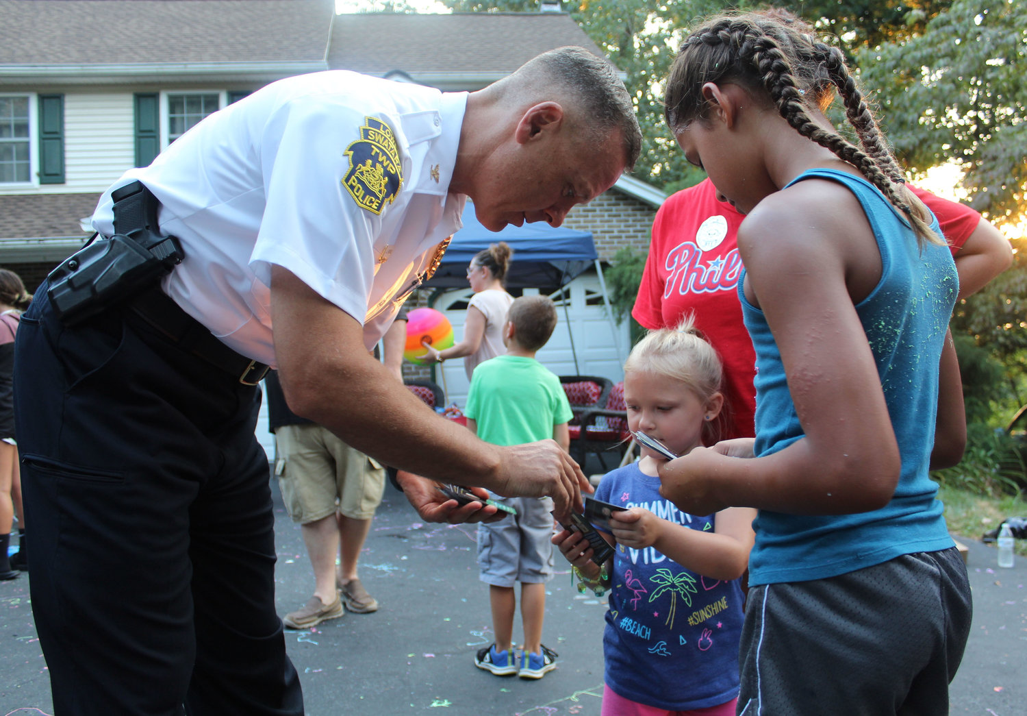 Lower Swatara Police Chief Jeff Vargo signs baseball cards for Rylee Miller and Safia Aman during National Night Out in Lower Swatara on Aug. 6.
