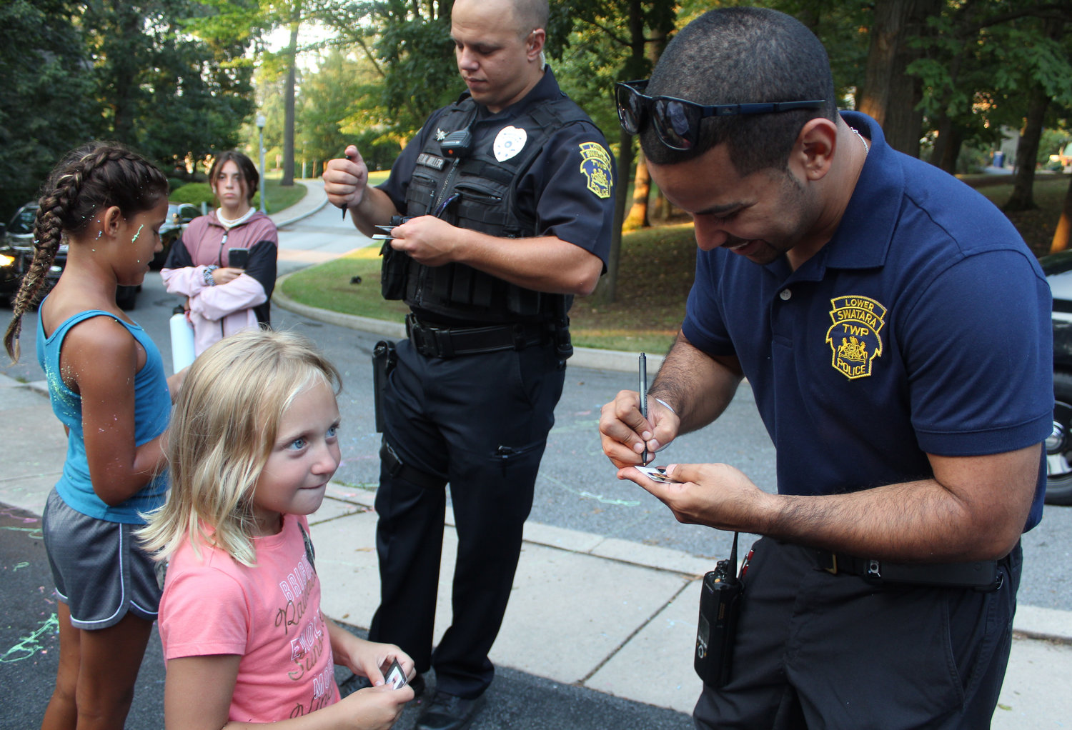 Lucy Stevenson waits for Detective Antonio Gonzalez Jr. to sign his baseball card during National Night Out in Lower Swatara on Aug. 6.