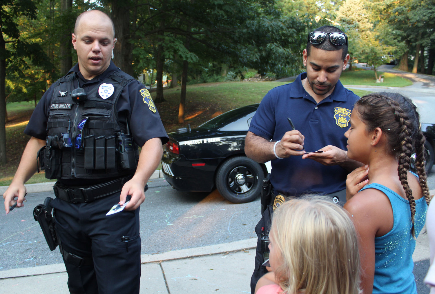 Lower Swatara Officer Jonathan Miller and Detective Antonio Gonzalez Jr. sign baseball cards for kids during National Night Out in Lower Swatara on Aug. 6.