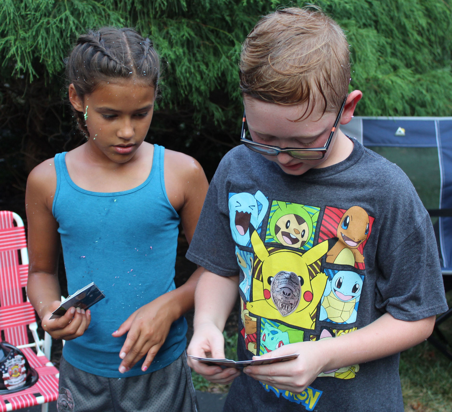 Safia Aman and Gabriel Shaver compare Lower Swatara officer baseball cards during National Night Out in Lower Swatara on Aug. 6.