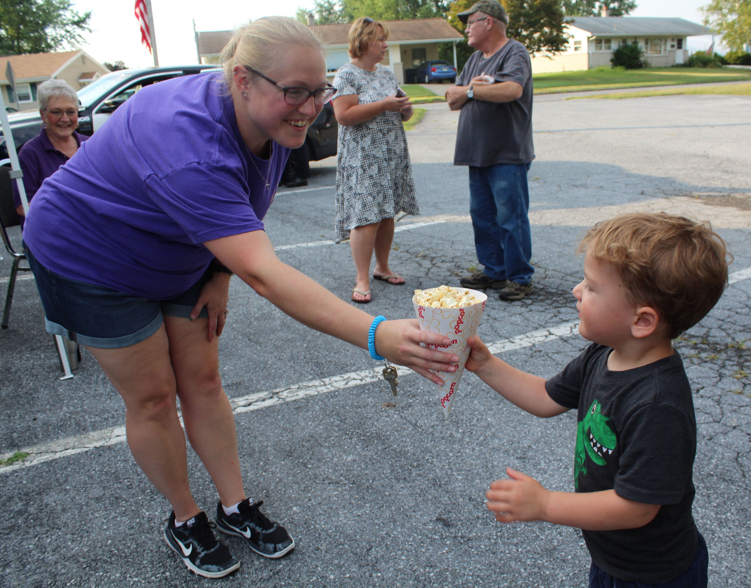 Lower Swatara Lion Kelsey Varner hands Jonas Lenguyel popcorn during National Night Out in Lower Swatara on Aug. 6.