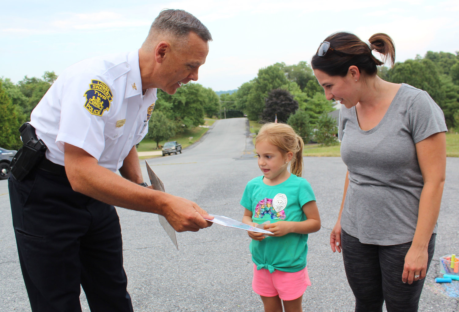Lower Swatara Police Chief Jeff Vargo gives Quinn and Rachel Felty a coloring book during National Night Out on Aug. 6.