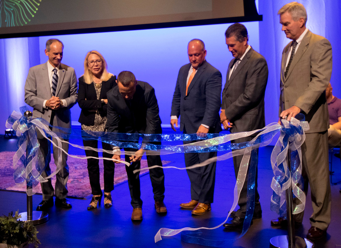 John Mason, Madlyn Hanes, Dr. Weston Kensinger, George P. Hartwick, Tom Mehaffie and Mike Bangs cut the ribbon for the Douglas W. Pollock Center for Addiction Outreach and Research on Aug. 21 during a ceremony at the Mukund S. Kulkarni Theatre at Penn State Harrisburg.