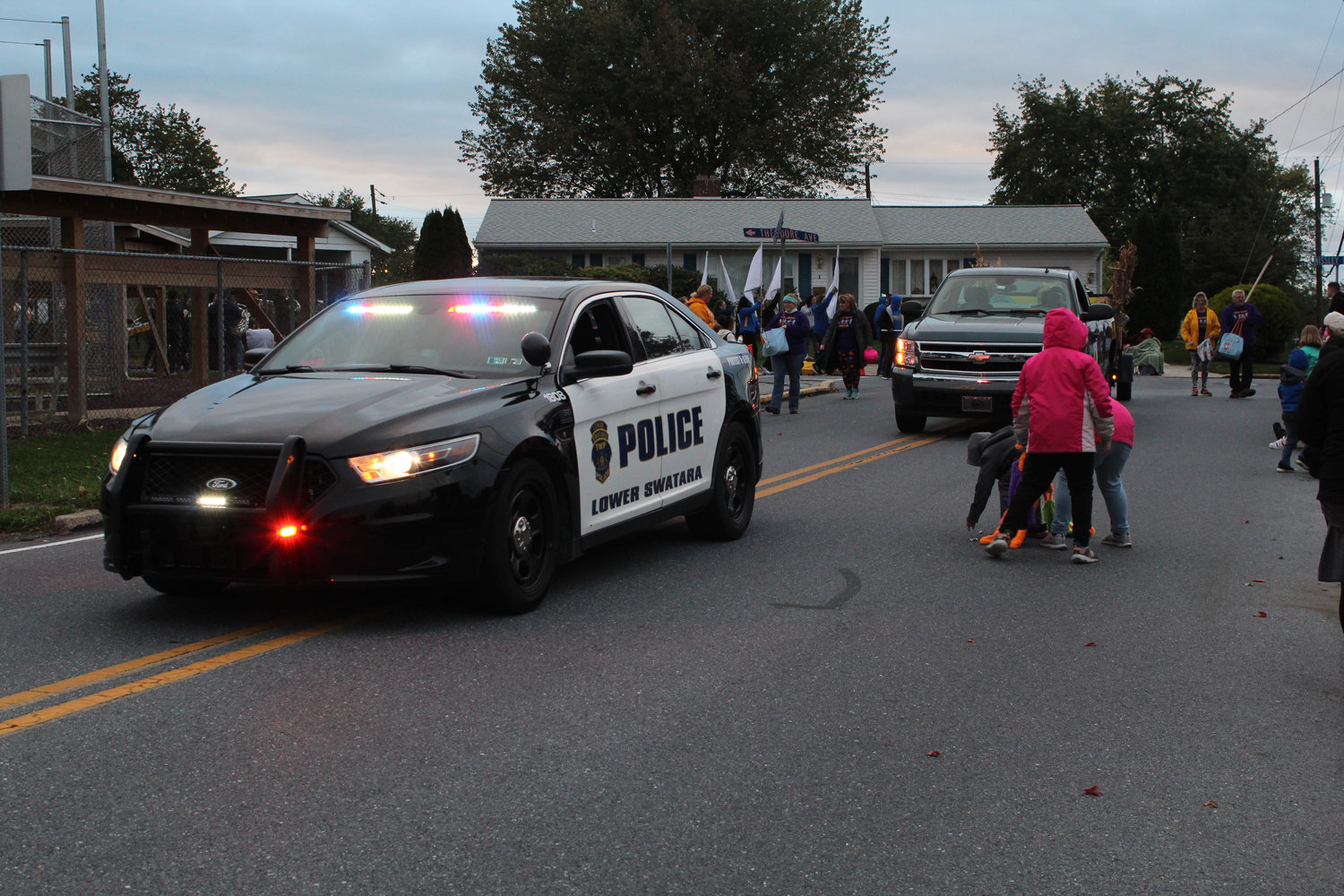 A Lower Swatara officer throws candy to kids during the Lower Swatara Halloween Parade on Oct. 17.