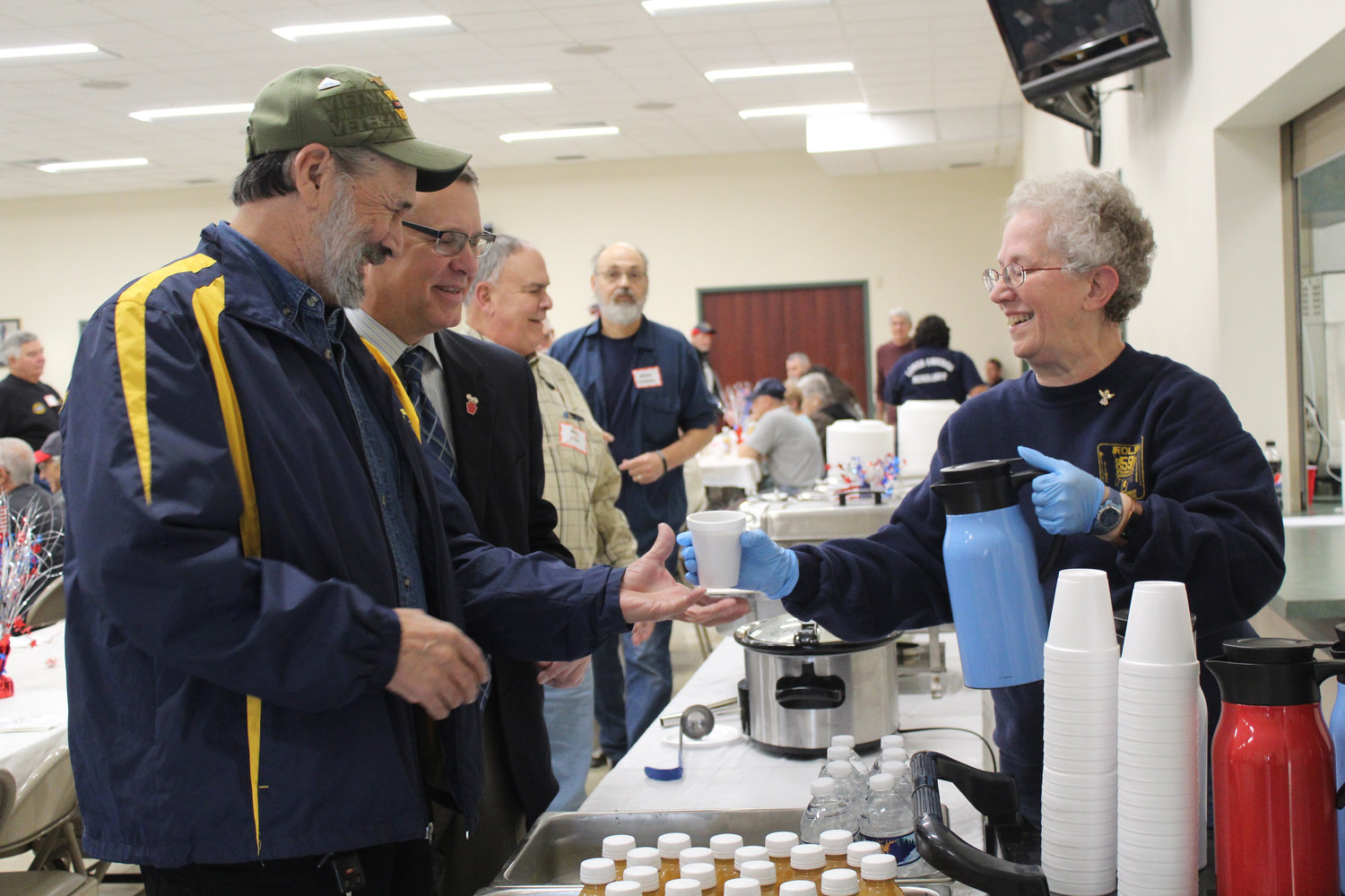 Betsy Dressler hands Navy veteran Mike Donnelly a cup of coffee during Rep. Tom Mehaffie's Veterans Breakfast at the Lower Swatara Fire Hall Nov. 8.